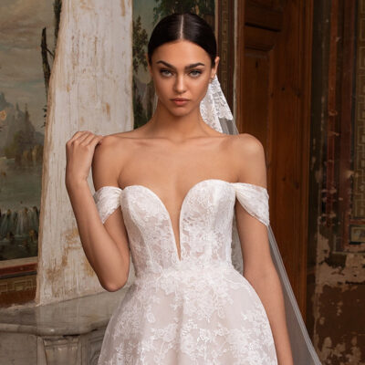 Bride using a floral patterns in Chantilly lace trace the off-the-shoulder sleeves, plunge neckline, and tulle princess skirt of this wedding gown, which combines the modern and the Victorian for an utterly timeless piece.